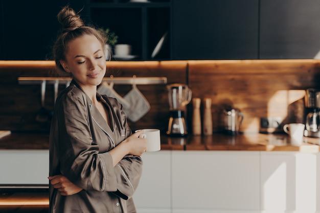 Красивая молодая счастливая женщина, стоящая в уютной шелковой пижаме на кухне с чашкой кофе