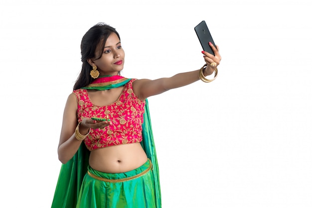 Beautiful young happy woman taking a selfie with clay lamp or diya during the festival of light diwali using a smartphone on white