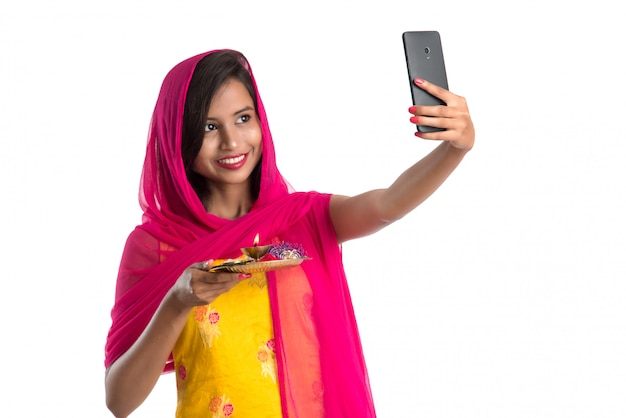 Beautiful young happy woman taking selfie with pooja thali using a mobile phone or smartphone on white