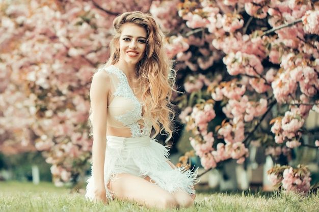 Beautiful young happy woman in white glamour dress in spring blossom park beauty girl on blooming sakura blossoms flowers on nature surface