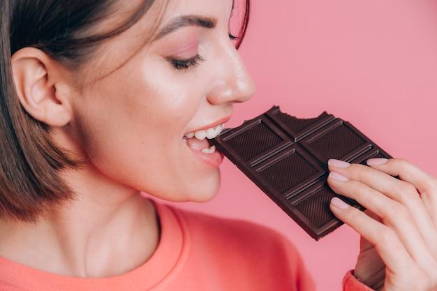 Bella giovane donna felice con una tavoletta di cioccolato su uno sfondo rosa e trucco luminoso, una cornice di primo piano prende un morso