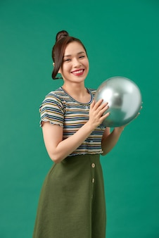 笑顔、緑の上の銀の風船と美しい若い幸せな女性
