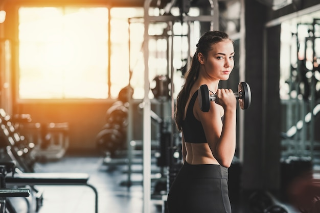 Beautiful young healthy caucasian woman holding dumbbell in gym
