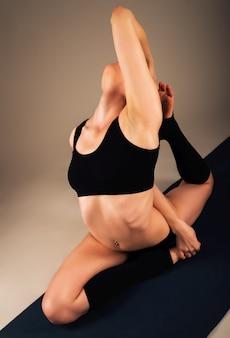 운동복을 입은 아름답고 건강한 소녀는 어두운 조명 아래 스튜디오 바닥에 앉아 있는 동안 다리 관절 운동을 합니다. 건강한 라이프 스타일 개념입니다. 광고 공간