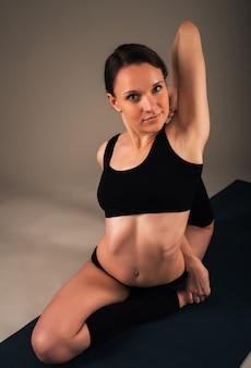 운동복을 입은 아름다운 젊은 건강한 소녀가 다리 관절 운동을 한다