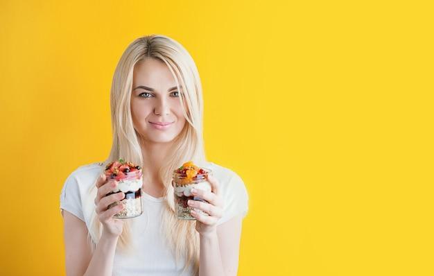 Красивая молодая здоровая девушка на ярком солнечном фоне с банками в руках. в банках овсяная каша и мюсли с фруктами, ягодами и крупами
