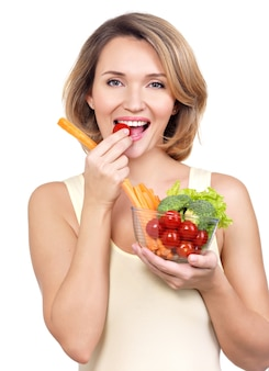 Beautiful young healthy woman eating a salad isolated on white.