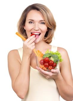 Bella giovane donna in buona salute che mangia un'insalata isolata su bianco.