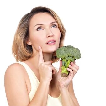 美しい若い健康な女性はブロッコリーを保持しています-白で隔離されます。