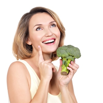 Beautiful young healthy woman holds broccoli isolated on white.