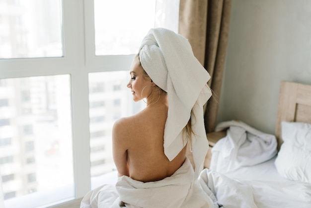 Beautiful young healthy woman relaxing in a robe, hotes, room and spa salon