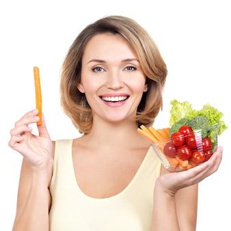 白で隔離野菜のプレートを持つ美しい若い健康な女性。