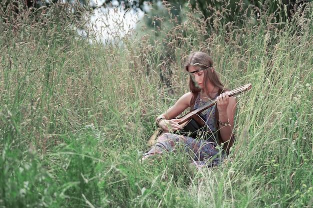 숲의 숲 사이의 빈 터에 앉아 기타를 연주하는 아름 다운 젊은 히피 여자