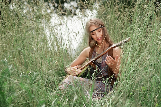 숲 숲 사이의 빈 터에 앉아 기타를 연주하는 아름 다운 젊은 히피 여자