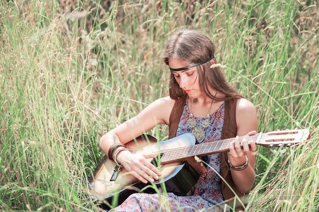 잔디에 앉아 기타를 연주하는 아름 다운 젊은 히피 여자
