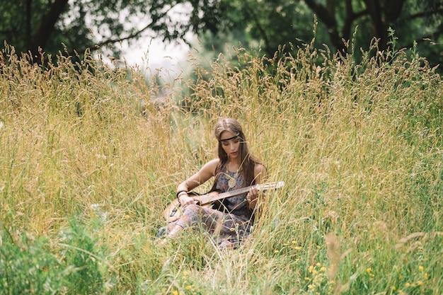 기타와 함께 아름 다운 젊은 히피 여자는 노래를 수행