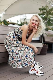 パターンとスタイリッシュな靴のベンチに座って瞬間を楽しんでいるファッショナブルなドレスの美しい若いヒップスターの女の子