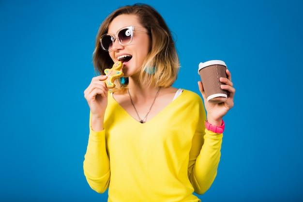 クッキーを食べて美しい若い流行に敏感な女性