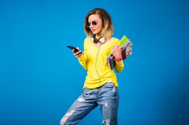 本を押しながらスマートフォンを見て美しい若い流行に敏感な女性