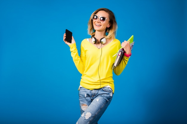Beautiful young hipster woman holding books and looking at smartphone