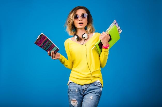 本を保持している美しい若い流行に敏感な女性
