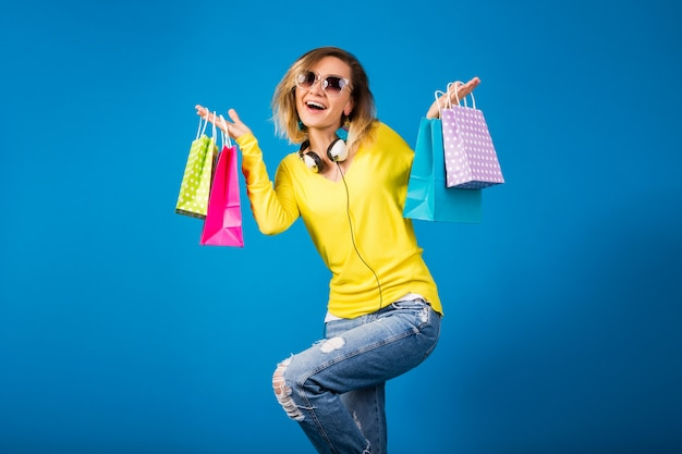 カラフルな紙の買い物袋を保持している美しい若い流行に敏感な女性