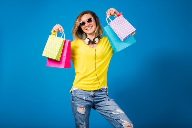 Красивая молодая хипстерская женщина, держащая красочные бумажные хозяйственные сумки