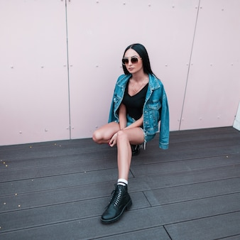 선글라스에 유행 가죽 검은 부츠에 티셔츠에 파란색 치마에 유행 데님 재킷에 아름 다운 젊은 hipster 여자는 도시에 금속 벽 근처에 앉아있다. 매력적인 소녀. 스트리트 스타일.