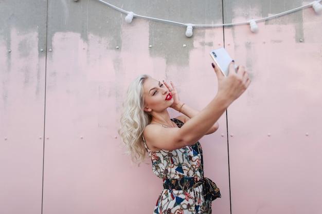 분홍색 벽 근처 전화에 selfie 하 고 유행 드레스에 아름 다운 젊은 hipster 여자. 소녀 블로거가 방송을