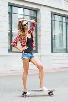 야외에서 스케이트 보드와 함께 포즈를 취하는 아름 다운 젊은 hipster 여자