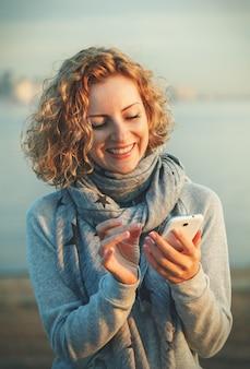 해변에서 스마트 휴대 전화를 사용 하여 아름 다운 젊은 hipster 여자