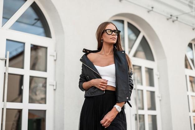 Красивая молодая хипстерская женщина с волосами на бровях в модных солнцезащитных очках в белой блузке в стильной кожаной черной куртке гуляет по улице возле белого здания. симпатичная девушка-модель отдыхает на открытом воздухе.