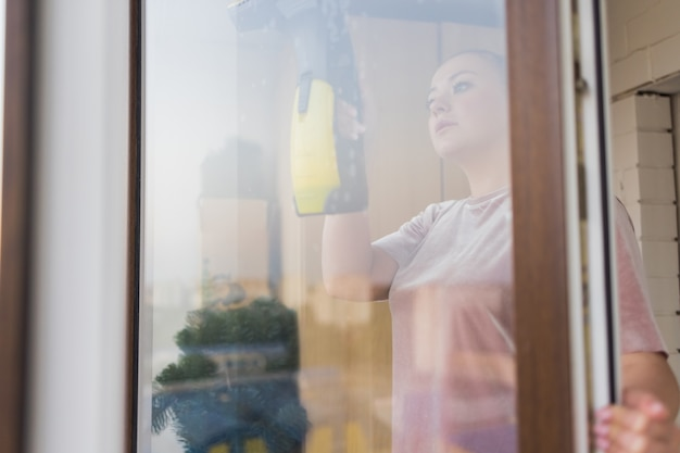 自宅でプロのツールで窓を洗う作業服の美しい若い主婦。