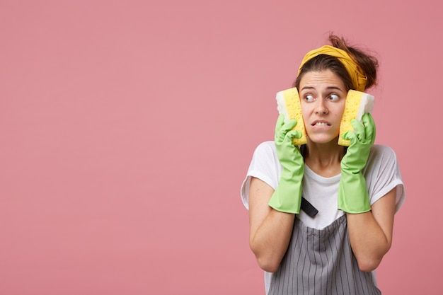 Beautiful young housewife looking sideways with scared terrified expression, holding sponges on her cheeks, feeling frustrated as she has to clean up whole dirty apartment by herself