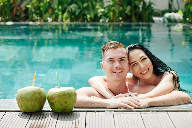 Beautiful young hugging couple leaning on edge of swimming pool next to coconut cocktails and smiling at front