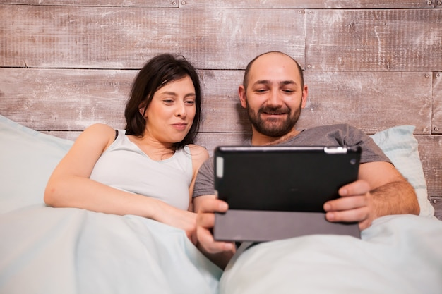 Beautiful young husband and wife wearing pajamas laughing while using tablet computer before bedtime.