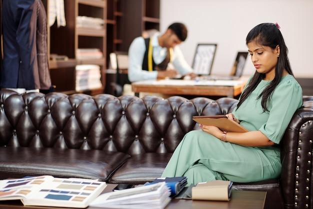 아틀리에 소파에 앉아 태블릿 컴퓨터에서 카탈로그를보고있는 아름다운 젊은 인도 여성