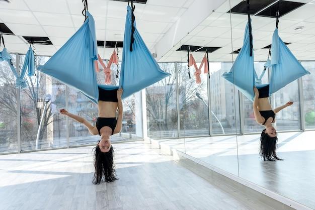 Красивый молодой инструктор, практикующий летать йогу в гамаке в тренажерном зале. упражнения для расслабления или здоровья