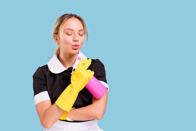 Beautiful young janitor holding spray bottle and blowing with eyes closed over blue background