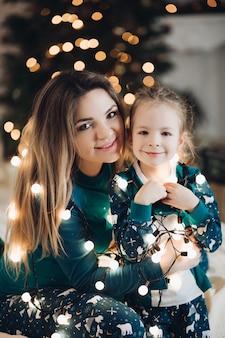 아름 다운 젊은 아가씨와 그들의 어깨 주위에 빛나는 크리스마스 불빛과 함께 사랑스러운 어린 소녀. 휴일 개념