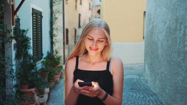Красивая молодая дама болтает на смартфоне во время прогулки по улице