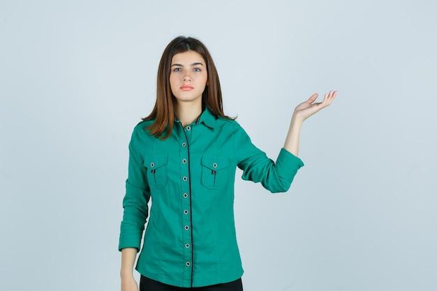 Bella giovane signora che fa gesto di benvenuto in camicia verde e guardando perplesso, vista frontale.
