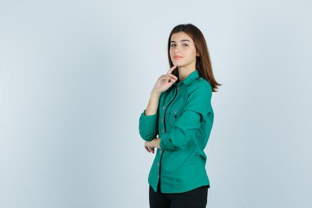 Bella giovane signora in camicia verde che tiene il dito sul mento e guardando fiducioso, vista frontale.