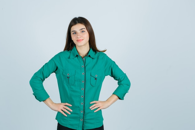 Bella giovane signora in camicia verde che tiene le mani sulla vita e che sembra sicura, vista frontale.