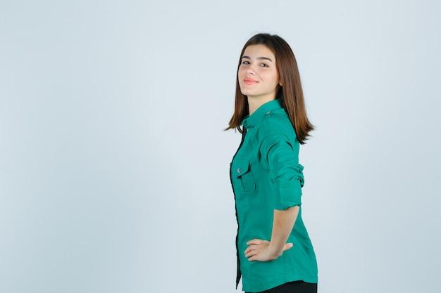 Bella giovane signora in camicia verde che tiene le mani sulla vita e che sembra sicura.