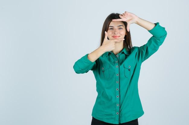 Bella giovane signora in camicia verde che fa gesto del telaio e che sembra allegro, vista frontale.