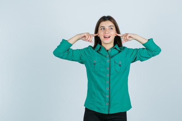 Bella giovane signora in camicia verde tappando le orecchie con le dita e guardando allegra, vista frontale.