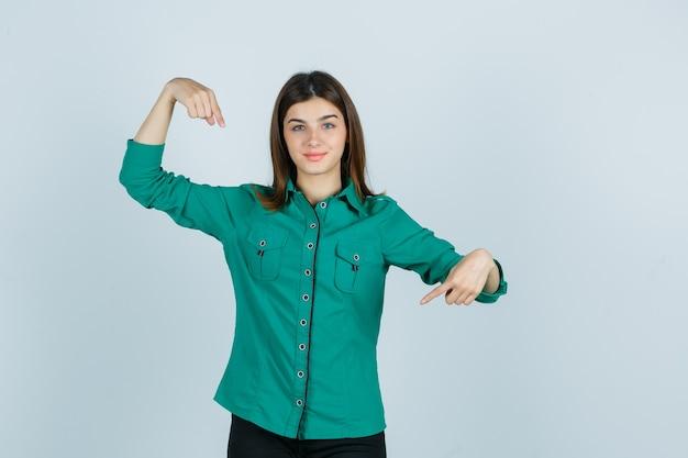 Bella giovane donna in camicia verde che punta a se stessa e guardando fiducioso, vista frontale.