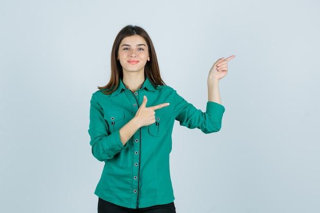 Bella giovane donna in camicia verde che punta a destra e sembra allegra, vista frontale.