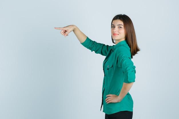 Bella giovane signora in camicia verde che punta dritto e sembra allegra.